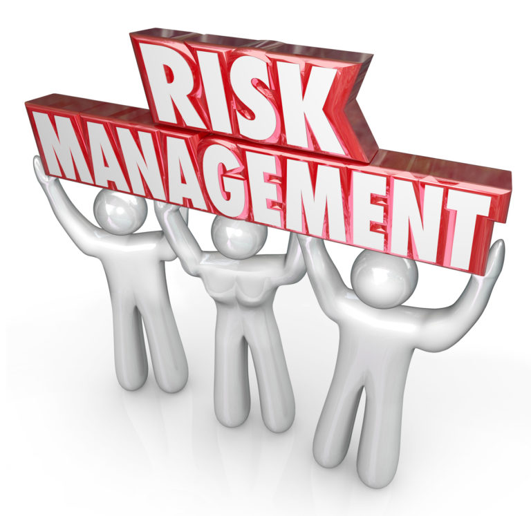 Risk Management words lifted by team of people or workers to illustrate a company or oranization's commitment to reducing risks and liability to damage and financial loss